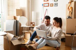 Ein fröhliches junges Paar sitzt auf dem Fußboden zwischen vielen Umzugskartons und nutzt einen Laptop