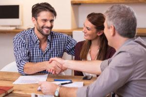 Ein glückliches Paar bedankt sich beim Finanzberater per Handschlag