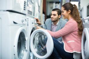 Eine junge Frau lässt sich zu einer Waschmaschine beraten