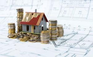 Auf einem Bauplan steht ein Modellhaus, das von vielen Münzstapeln eingerahmt wird
