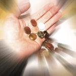Aus einer offenen Hand fallen Münzen herab