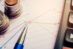 Ein Stift liegt auf einem Blatt mit Datenlinien, audf dem auch zwei Münzstapel stehen