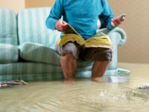 Ein Mann sitzt auf einem Sofa das im Hochwasser seiner Wohnung steht und sucht in den gelben Seiten nach einer Telefonnummer