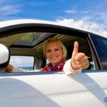 Autofahrerin streckt Arm aus dem Fenster und zeigt den Daumen nach oben