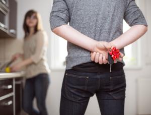 Ein Mann versteckt einen Autoschlüssel mit Geschenkschleife hinter seinem Rücken vor seiner Frau