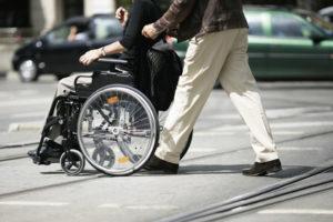 Jemand schiebt eine Person im Rollstuhl über die Straße