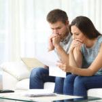 Ein junges Paar sitzt auf der Couch und grübelt über die Unterlagen vor Ihnen
