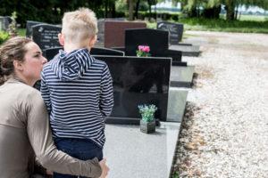 Eine Mutter und ihr Sohn stehen an einem Grab