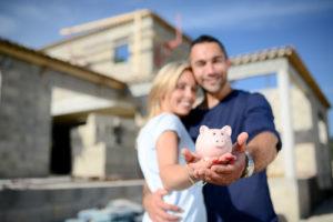 Ein Paar hält sich im Arm, streckt ein Sparschwein vor und steht dabei vor einem Rohbau