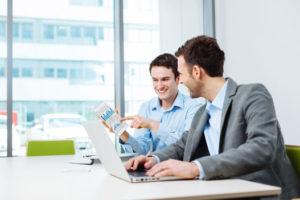 Zwei junge Geschäftsmänner lachen und nutzen ein Smartphone und einen Laptop