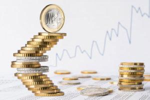 Treppenartig nach rechts oben gebauter Euro Münzstapel vor einem postiv laufenen Linienchart