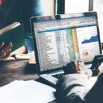 Ein Mann mit Anzug sitzt vor einem Laptop mit Daten und Diagrammen auf dem Bildschirm