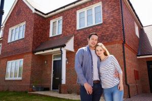 Ein glückliches junges Paar steht vor einem schönen Haus aus roten Klinkersteinen