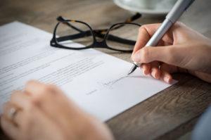Jemand unterschreibt einen Vertrag, daneben liegt eine Brille auf dem Tisch