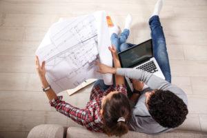 Junges Paar studiert einen Bauplan und nutzt einen Laptop