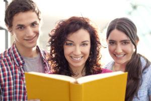 Drei lächelnde Leute halten ein aufgeschlagenes Buch vor sich