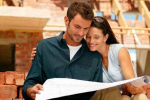 Ein fröhliches Paar studiert einen Bauplan und steht vor einem Rohbau