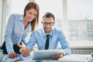 Eine junge Frau berät einen jungen Geschäftsmann, der einen Tablet-Computer nutzt