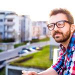 Junger Mann mit Bart und Brille steht auf einem Balkon und blickt erwartungsvoll in die Ferne