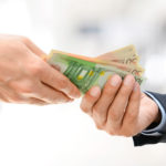Eine Männerhand im Anzug überreicht einer anderen einige Geldscheine