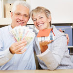 Fröhliches älteres Paar hält ein Modellhaus und Bargeld vor sich