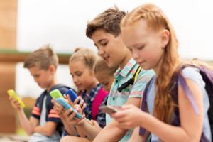 Vier Grundschuldkinder, die mit ihren Smartphones spielen