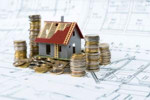 Auf einem Bauplan steht ein Modellhaus mit nur halb fertigem Dach sowie einige Euro-Münzen