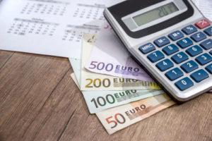 Auf einem Tisch liegen ein Kalenderblatt ein Taschenrechner und einige Euro Geldscheine