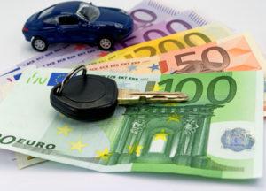 Ein Spielzeug-Porsche und ein Autoschlüssel liegen auf einigen Euro Geldscheinen