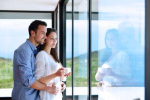 Ein glückliches junges Paar blickt gemeinsam verträumt durch eine große Fensterfront