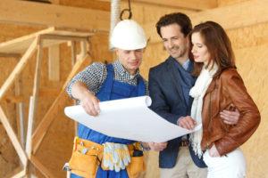 Glückliches Paar und Handwerker mit Bauplan auf der Baustelle für ein Holzhauses