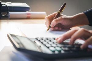 Jemand benutzt einen Taschenrechner und macht sich mit einem Füller Notizen