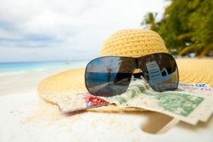 Ein Sommerhut mit Sonnenbrille und einigen Geldscheinen liegt auf dem Sandstrand