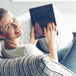 Auf der Couch lehnt eine junge lächelnde Frau mit einem Tablet Computer