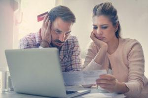 Ein besorgtes Paar studiert das Kleingedruckte eines Vertrags und nutzt einen Laptop