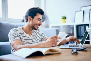 Ein lächelnder junger Mann sitzt am Couchtisch und beantragt über seinen Laptop einen Kredit