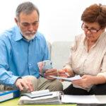 Ein älteres Paar studiert Unterlagen, nutzt einen Taschenrechner und er hält einige Euroscheine in einer Hand