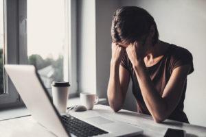 Eine Frau sitzt verzweifelt an einem Schreibtisch vor einem aufgeklappten Laptop
