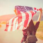 Eine gelöste junge Frau in der Natur lässt eine US-Flagge wehen