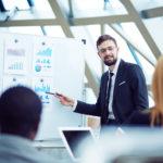Junger Geschäftsmann erklärt Statistiken am Whiteboard