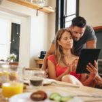 Ein junges Paar sitzt in der Küche am Tisch und nutzt einen Tablet Computer