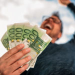 Ein jubelnder Mann hält mehrere 100 Euro Scheine in der Hand und streckt die Faus gen Himmel