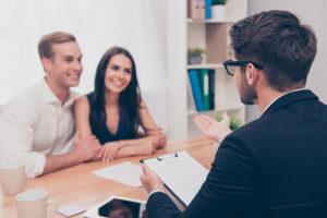 Ein Kreditberater sitzt in seinem Büro am Schreibtisch zusammen mit einem jungen, lächelnden Paar.