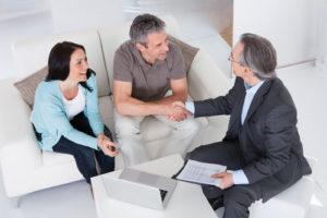 Ein Ehepaar sitzt mit einem Kreditberater am Tisch und führt ein geschäftliches Gespräch