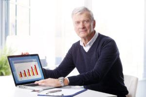 Ein Mann zeigt ein ansteigendes Balkendiagramm auf einem Laptop