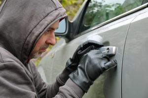 Ein Mann mit Kaputzenpulli und Handschuhen versucht ein Autoschluss zu knacken