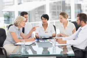 Mehrere Geschäftsleute sitzen diskutierend am Glastisch