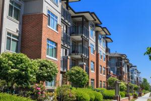 Neue Wohnhäuser mit Vorgärten im Sonnenschein