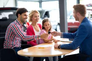 Eine lachende Familie nimmt beim Autohändler einen Autoschlüssel entgegen
