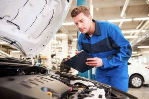 Ein junger Mechaniker hält ein Klemmbrett und checkt den Motorraum eines Autos